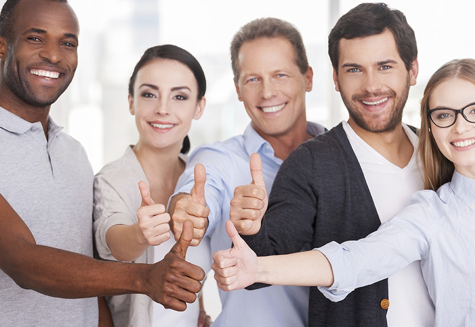 group of 5 employees smiling at camera giving thumbs up