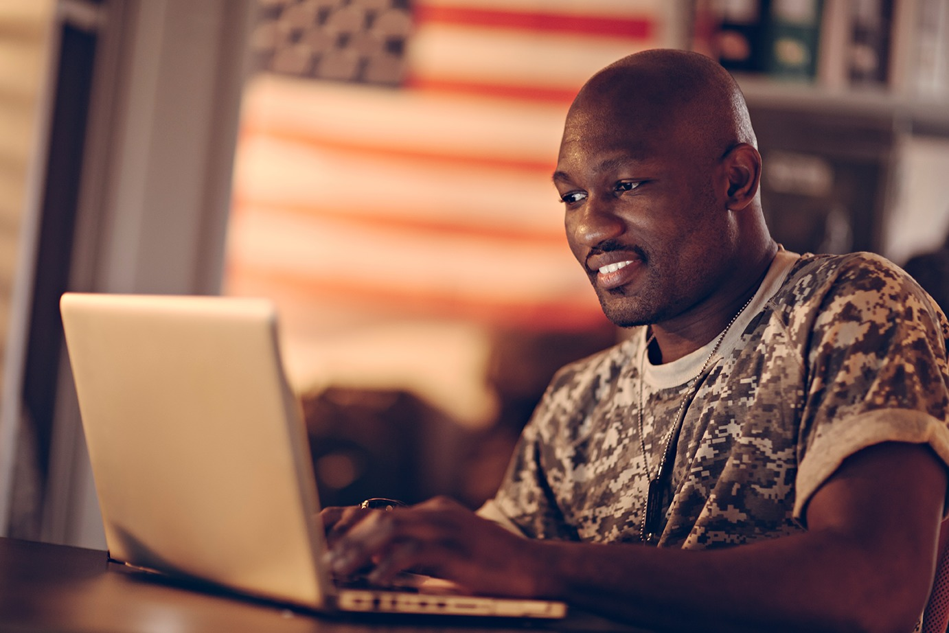 Serviceman wearing camo shirt and dog tags, working on laptop, American flag in the background