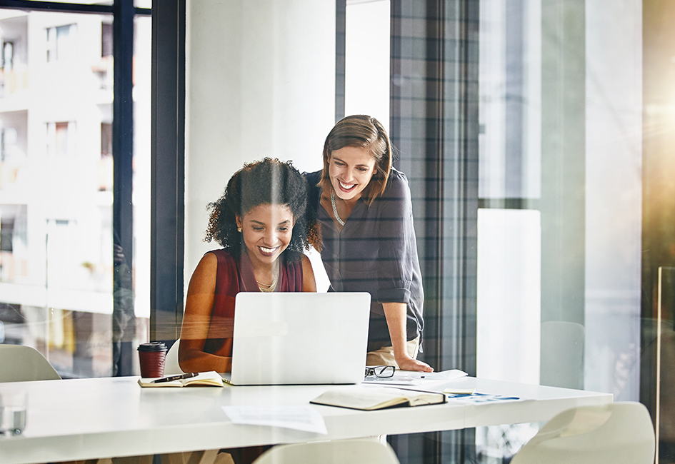 2 business women similing at computer