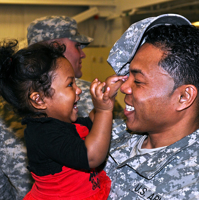 military father in uniform holding young daughter both smiling