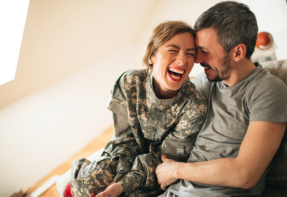 Military women in uniform laughing with husband