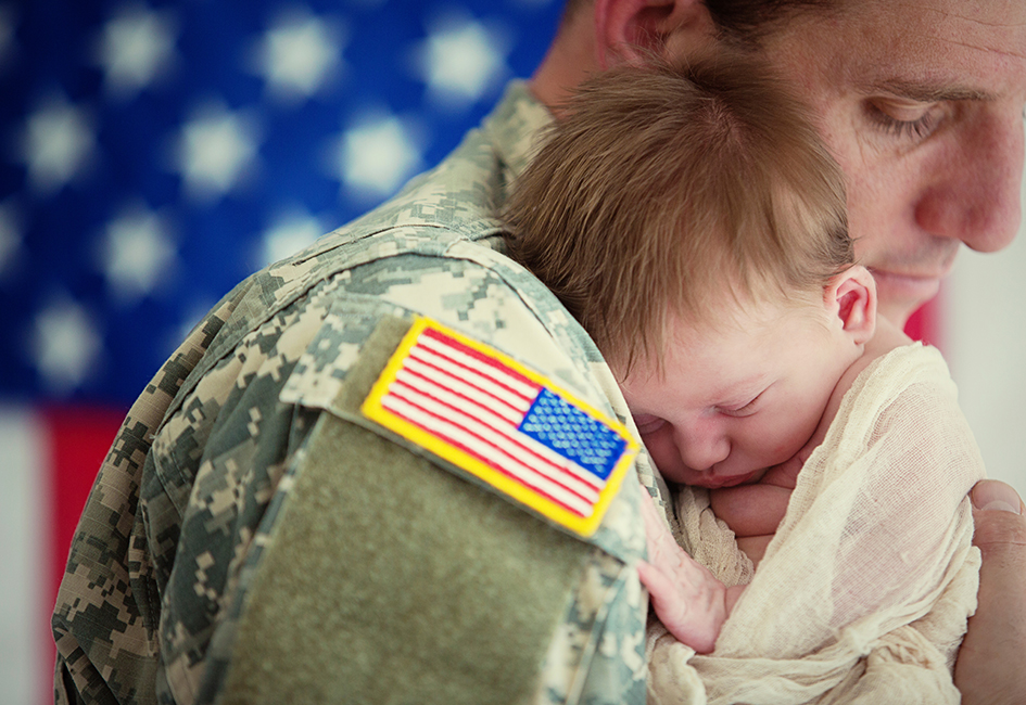 military father in uniform holding very young child
