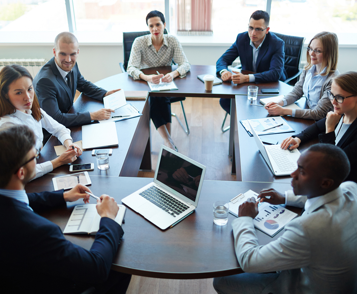 group of 8 employees sitting around table in office having a meeting