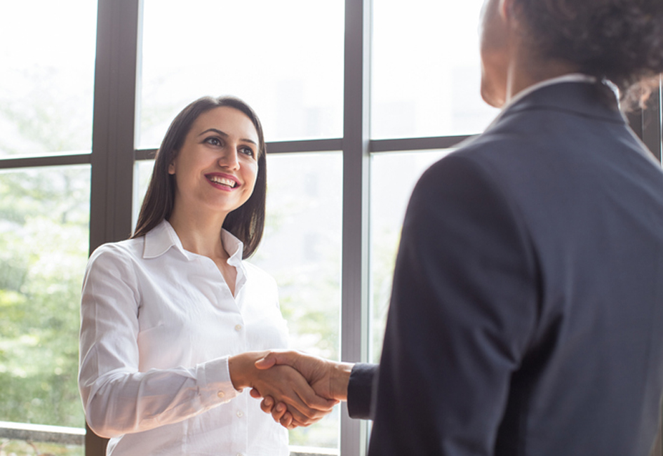 Cheerful confident female manager concluding deal with handshake