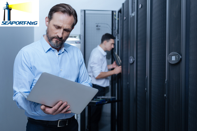 2 businessmen standing by lockers, one looking into locker, other holding and looking at laptop