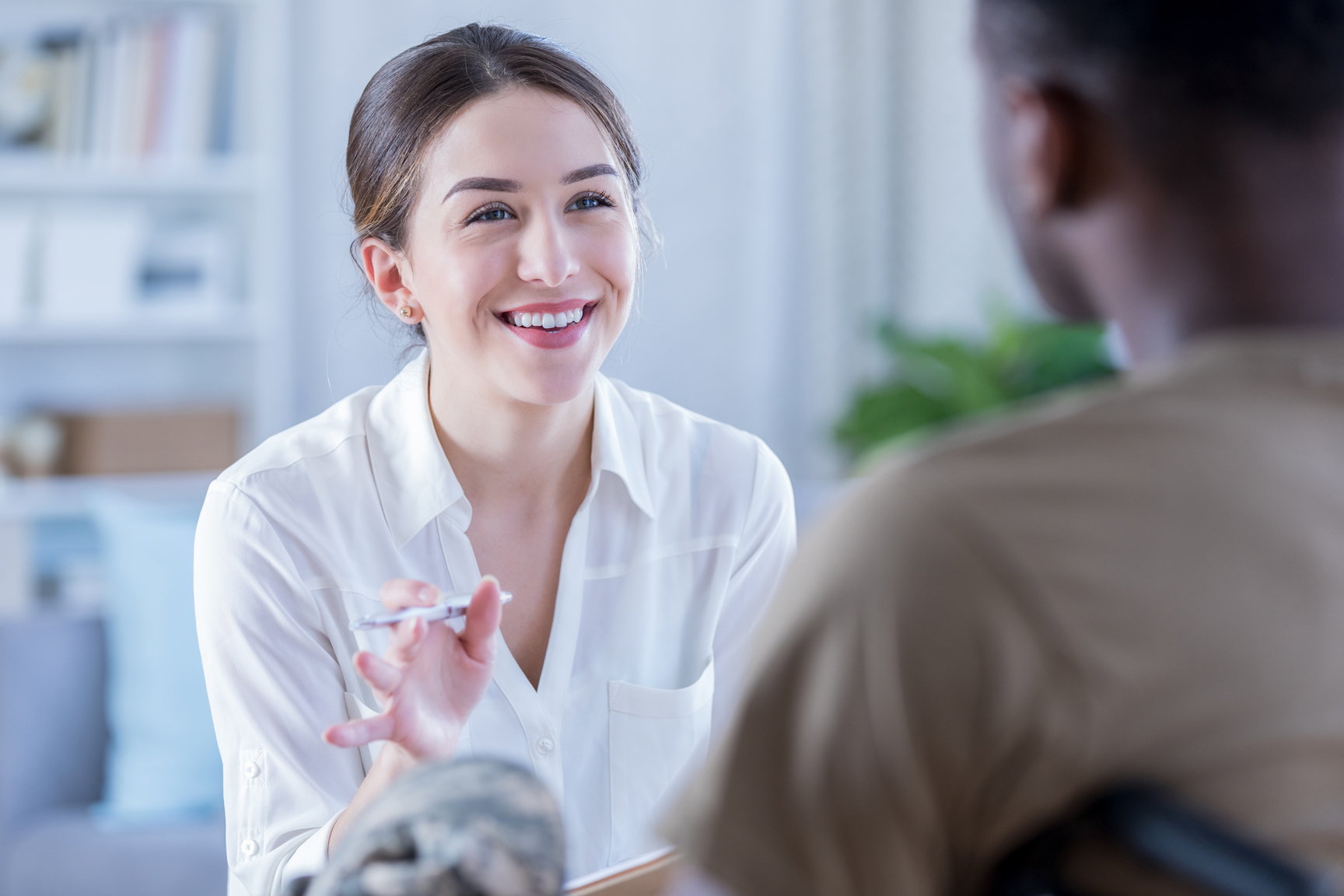 Young business women smiling at service memeber, engaged in conversation