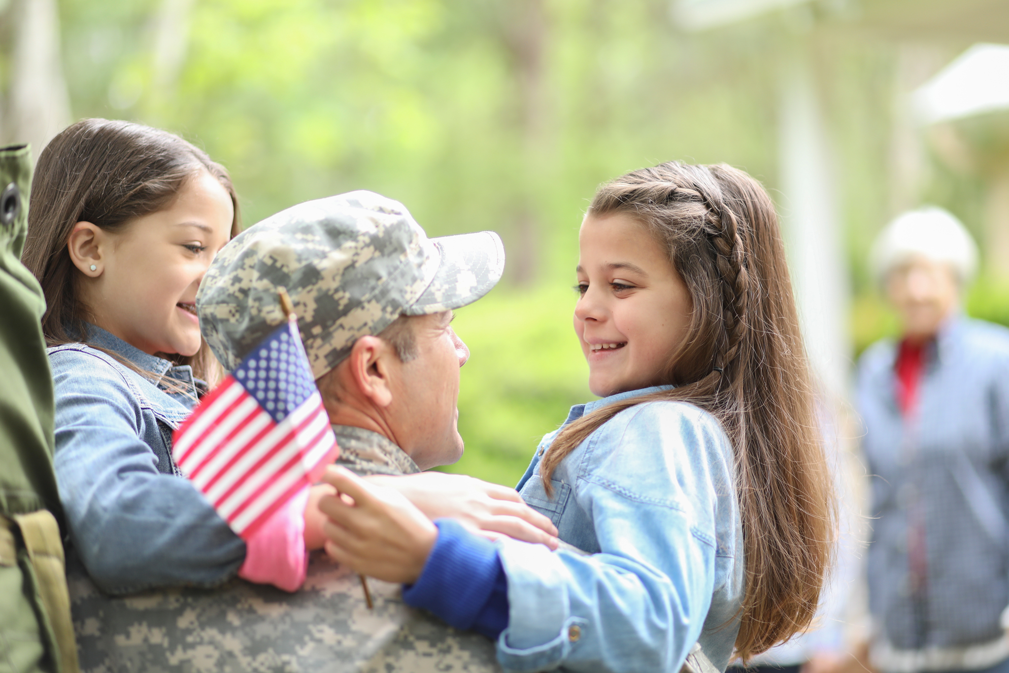 Military father in uniform with younger children holding American flag