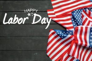 Black wooden background with small American flags on right side, text reads Happy Labor Day