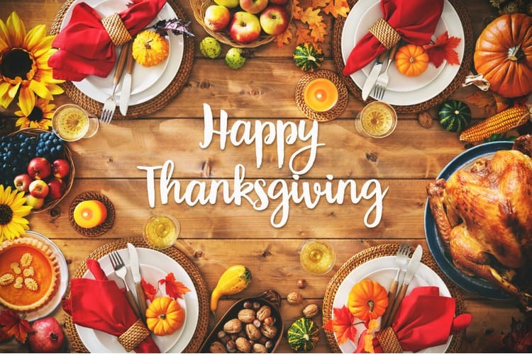 """Thanksgiving dinner laid out on the wooden dinner table. """"Happy Thanksgiving"""" written in white text in the center of the image."""