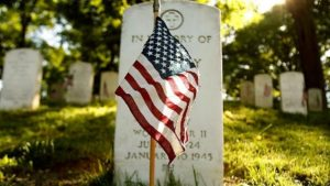 American flag standing in front of military tombstone.