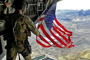 Army soldier flying American flag out of the back of a helicopter